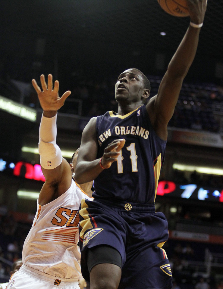 Photo - New Orleans Pelicans point guard Jrue Holiday (11) scores against the Phoenix Suns in the first quarter during an NBA basketball game on Sunday, Nov. 10, 2013, in Phoenix. (AP Photo/Rick Scuteri)