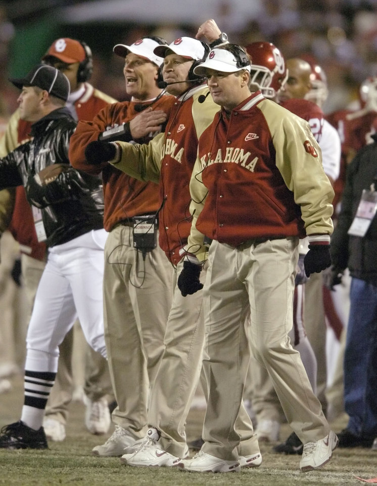 Kansas City, MO. USA.  Saturday, December 6, 2003:  Big 12 Championship College Football  Arrowhead Stadium, University of Oklahoma vs Kansas State University (KSU):   OU coaches Brent Venables, Mike and Bob Stoops  send signals to their defense.   Staff photo by Steve Sisney.