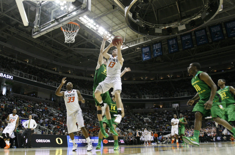 Photo - OSU's Phil Forte goes up for a shot over E. J. Singler Oregon's in the second round of the NCAA Basketball tournament in San Jose, CA, Mar. 21, 2013. STEPHEN PINGRY/Tulsa World
