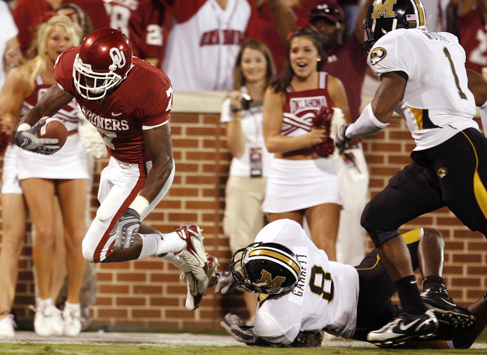 Photo - Oklahoma's DeMarco Murry (7) is tripped up by Missouri's Justin Garrett (8) during the second half of the college football game between the University of Oklahoma Sooners (OU) and the University of Missouri Tigers (MU) at the Gaylord Family Oklahoma Memorial Stadium on Saturday, Oct. 13, 2007, in Norman, Okla.By STEVE SISNEY, The Oklahoman