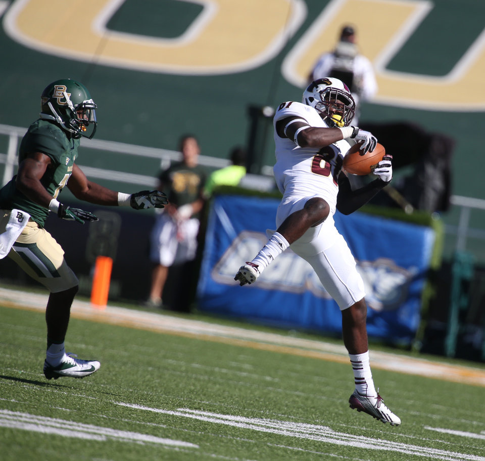 Photo - Louisiana-Monroe wide receiver Rashon Ceaser, right, pulls down a pass in front of Baylor safety Terrell Burt during the first half of a NCAA college football game, Saturday, Sept. 21, 2013, in Waco, Texas. (AP Photo/Waco Tribune Herald, Rod Aydelotte)