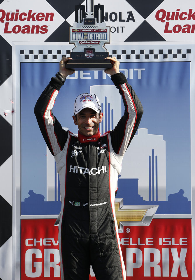Photo - Helio Castroneves holds up the winners trophy after the second race of the IndyCar Detroit Grand Prix auto racing doubleheader in Detroit Sunday, June 1, 2014. (AP Photo/Bob Brodbeck)
