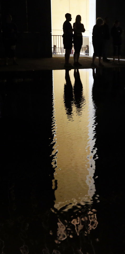 Photo - People under the 9:03 Gate of Time are reflected in water at the Oklahoma City National Memorial before the Oklahoma City Memorial Marathon in Oklahoma City, Sunday, April 24, 2016. Photo by Nate Billings, The Oklahoman
