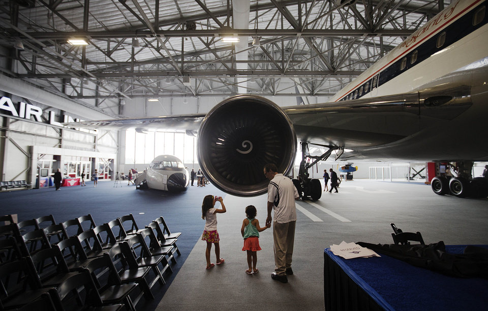 Photo - Carson Perry, 4, center, holds the hand of her grandfather Charles Swaney, while looking at the engine of a Boeing 767 airplane with her sister Chandler, 7, left, at the grand opening of the new Delta Flight Museum, Tuesday, June 17, 2014, in Atlanta. Delta Air Lines is re-opening a museum at its Atlanta headquarters after extensive renovations in hopes of luring tourists to the company's original aircraft maintenance hangars on the north edge of the world's busiest airport. The 68,000-square-foot museum, housed in hangers that date to the 1940s, traces Delta's history from crop-dusting and air mail service to its first passenger flight from Dallas to Jackson, Mississippi, on June 17, 1929. (AP Photo/David Goldman)