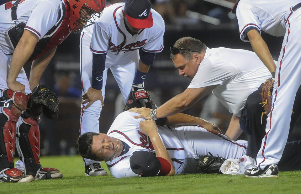 Atlanta Braves relief pitcher Luis Avilan is is tended to after going down during the eighth inning of a baseball game against the Kansas City Royals, Tuesday, April 16, 2013, in Atlanta. (AP Photo/John Amis)