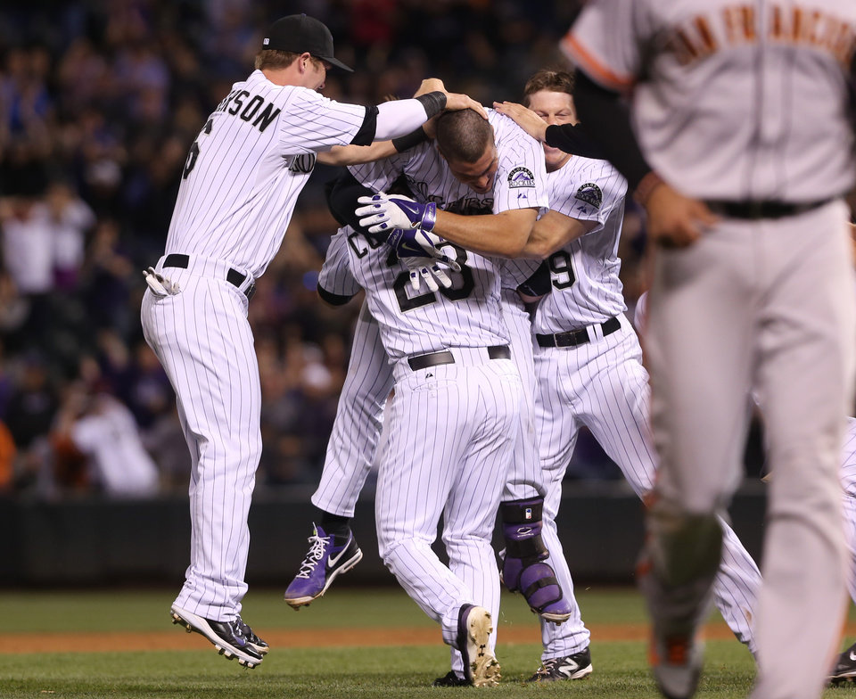 Photo - Colorado Rockies' Nolan Arenado, second from left on top, celebrates his walkoff double to drive in two runs with teammates, from left, Corey Dickerson, Charlie Culberson and DJ LeMahieu against the San Francisco Giants in the ninth inning of the Rockies' 5-4 victory in a baseball game in Denver on Tuesday, May 20, 2014. (AP Photo/David Zalubowski)