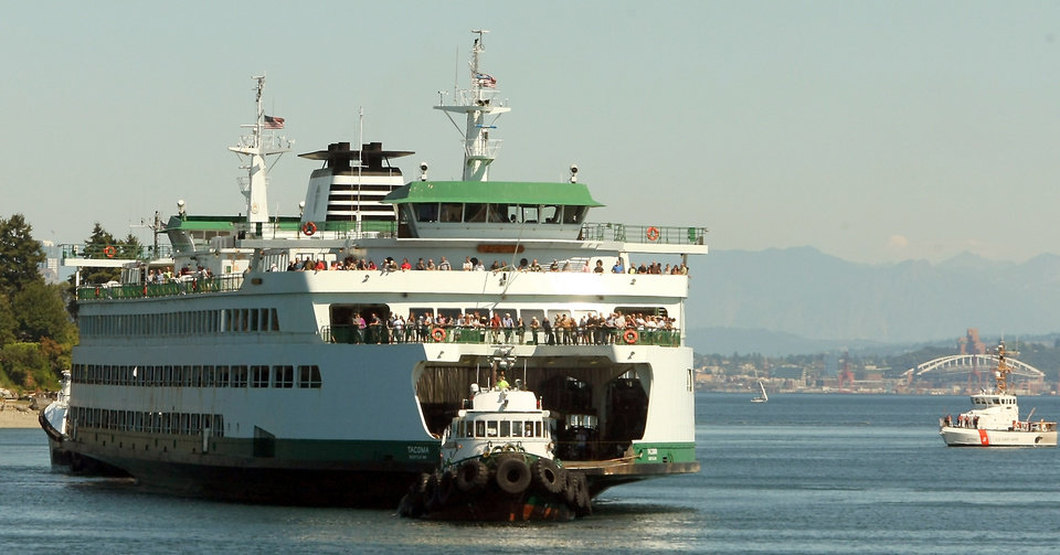 Photo - Tugboats bring the M/V Tacoma to dock after it lost power while traveling from Seattle to Bainbridge Island, Washington on Tuesday, July 29, 2014. (AP Photo/Kitsap Sun, Meegan M. Reid)
