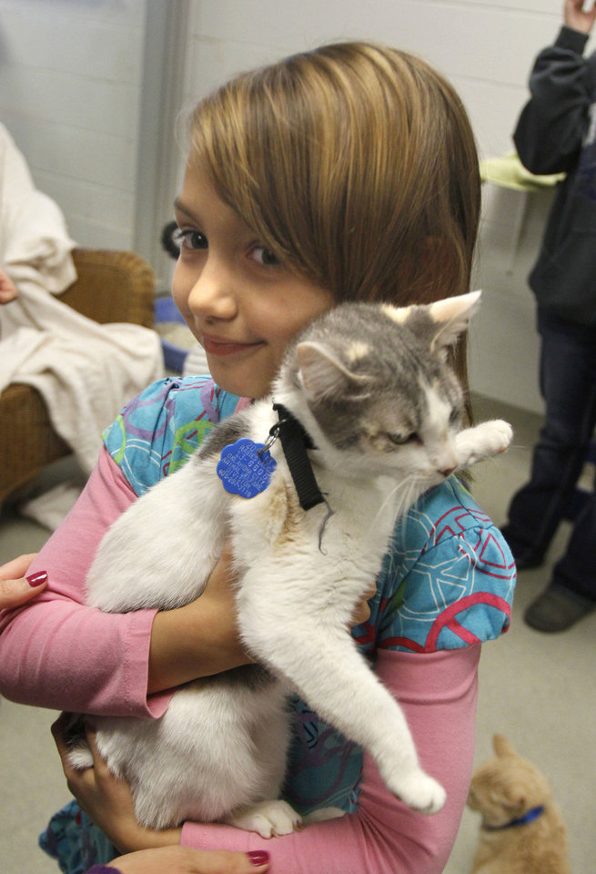 Right: Robin Miller, 6, holds her adopted kitten.