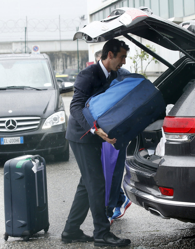 Photo - Italy goalkeeper Gianluigi Buffon loads his luggage onto a car upon his arrival with his teammates at Malpensa airport after landing from Brazil, in Milan, Italy, Thursday, June 26, 2014. Italy was disqualified from the World Cup after loosing to Uruguay in their group stage round.  (AP Photo/Luca Bruno)