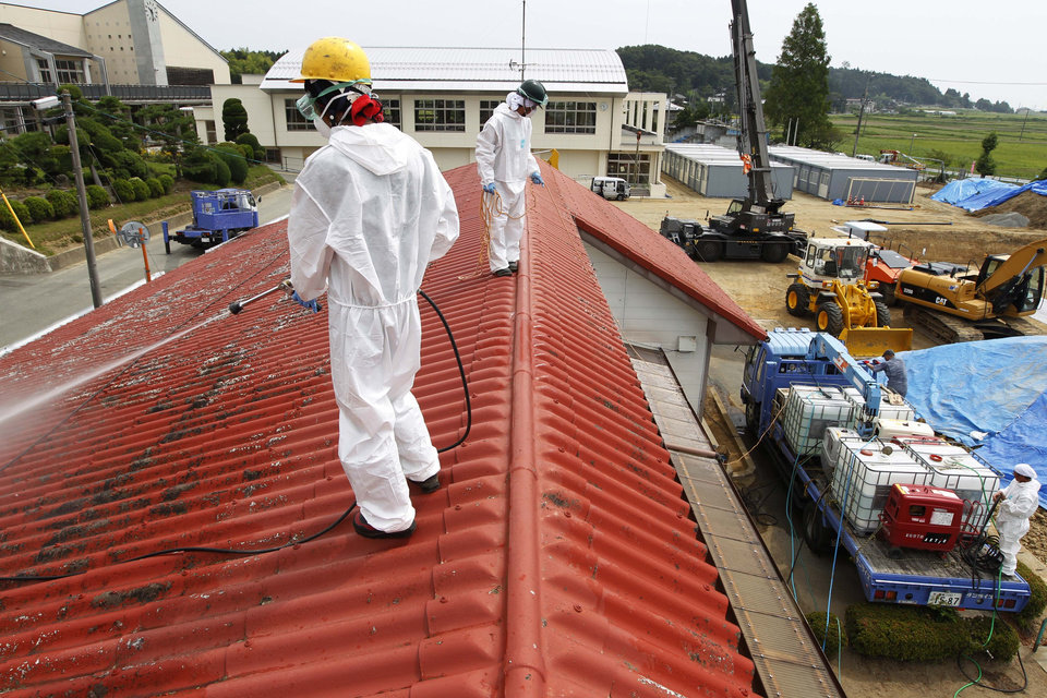 FILE - In this Aug. 18, 2011 file photo, workers in white radiation protective suits, go through an operation to decontaminate radiation from the roof of Yasawa Kindergarten in Minami-Soma, about 12 miles (20 kilometers) away from the tsunami-crippled Fukushima Dai-ichi nuclear facility, in Fukushima prefecture, northeastern Japan. Influential Japanese scientists who help set national radiation exposure limits have for years had trips paid for by the country�s nuclear plant operators to attend overseas meetings of the world�s top academic group on radiation safety. Some of these same scientists have consistently given optimistic assessments about the health risks of radiation, interviews with the scientists and government documents show. Their pivotal role in setting policy after the March 2011 tsunami and ensuing nuclear meltdowns meant the difference between schoolchildren playing outside or indoors and families staying or evacuating.  (AP Photo/Hiro Komae, File)