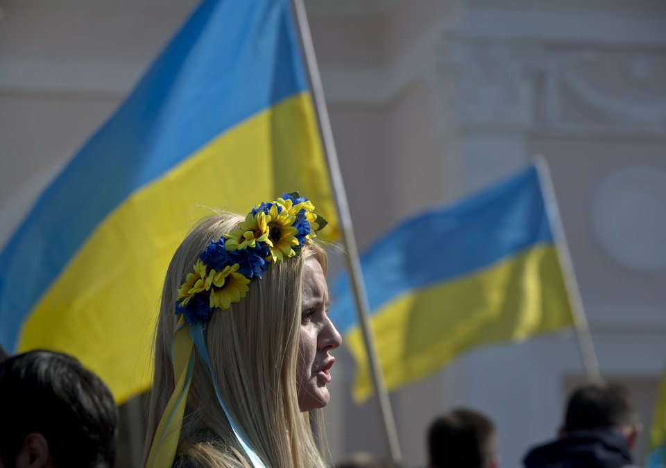 Photo - A pro-Ukrainian demonstrator attends a rally, back dropped by Ukraine's nation flag, in Simferopol, Ukraine, Saturday, March 15, 2014. Tensions are high in the Black Sea peninsula of Crimea, where a referendum is to be held Sunday on whether to split off from Ukraine and seek annexation by Russia. (AP Photo/Vadim Ghirda)