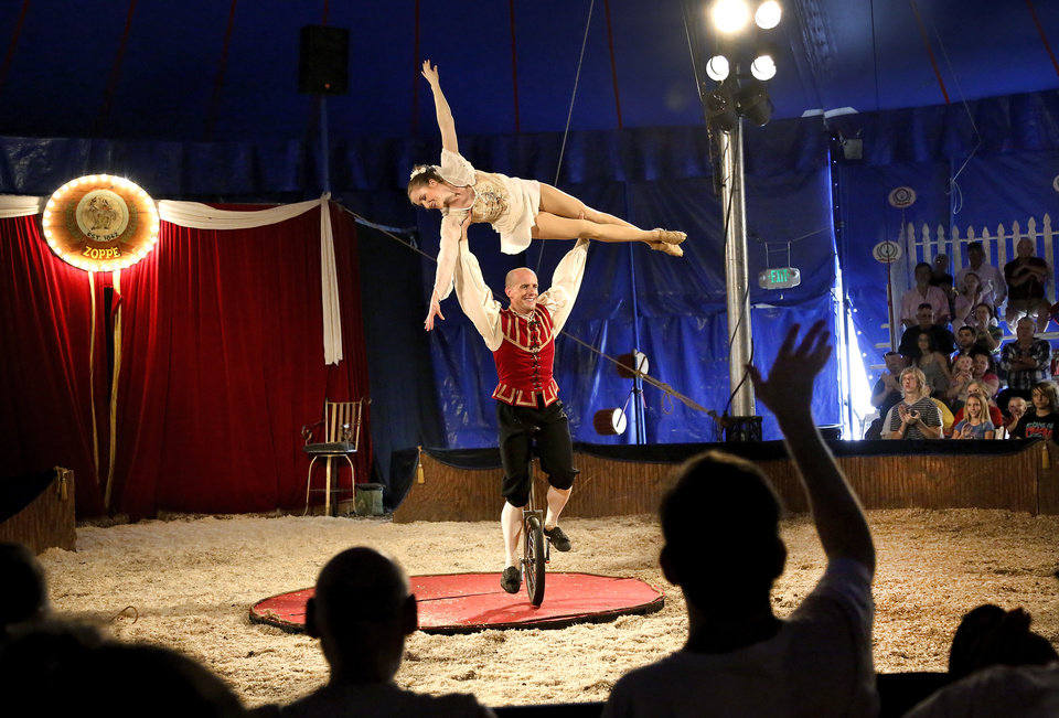 Photo - Nick Harden lifts Wendy Allen above his head while balanced on a unicycle.  Harden and Allen are among the performers in the Zoppe Italian Family Circus who entertained a crowd of about 500 fairgoers under the big top tent in the Centennial Plaza at the Oklahoma State Fair on Wednesday, , Sep. 18, 2013. Photo  by Jim Beckel, The Oklahoman.