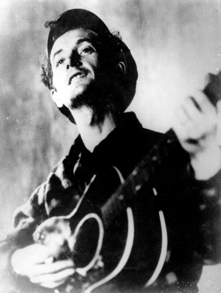 "FILE - This undated file photo shows folk singer Woody Guthrie playing his guitar.  Guthrie's writings, recordings and artwork will land in his native state after an Oklahoma foundation bought the collection, with plans for a display that concentrates on his artistry rather than the populist politics that divided local opinion over the years. Guthrie, known for the anthem, ""This Land is Your Land"" and his songs about the poor and downtrodden, is remembered mostly as a musician, composer and singer, but was also a literary figure and an artist, said Bob Blackburn, executive director of the Oklahoma Historical Society.   (AP Photo/File) ORG XMIT: CER101"