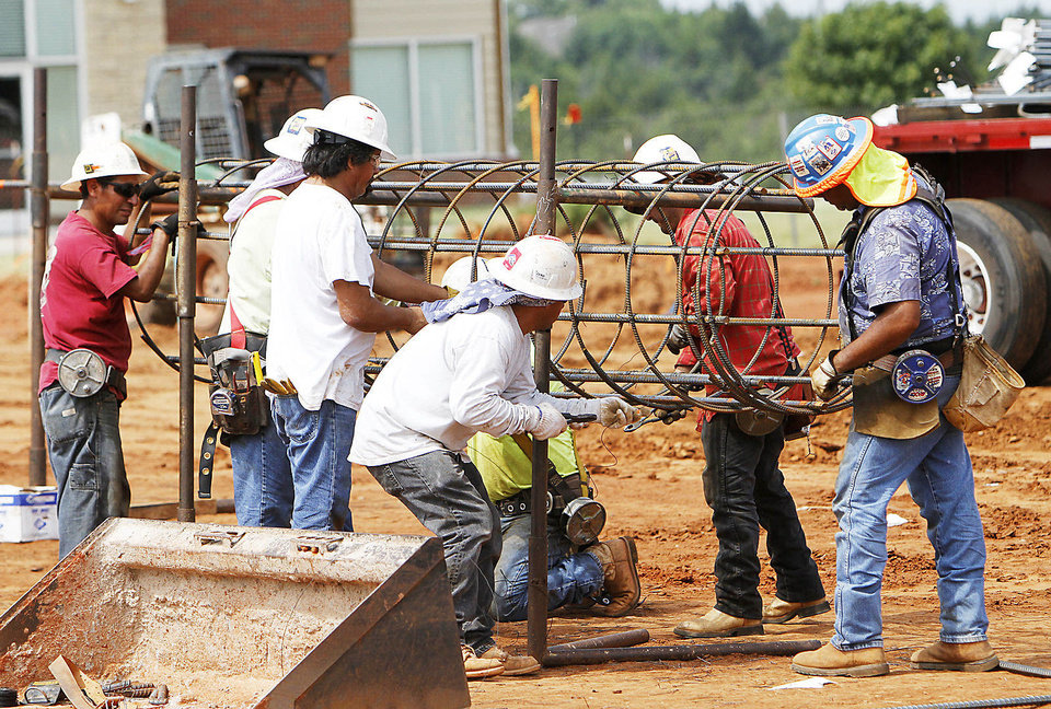 Photo - Construction workers tie rebar to reinforce one of the 250 piers being poured at the site of the new $22.5 million Edmond Recreation and Aquatic Center. PHOTO BY DAVID MCDANIEL, THE OKLAHOMAN