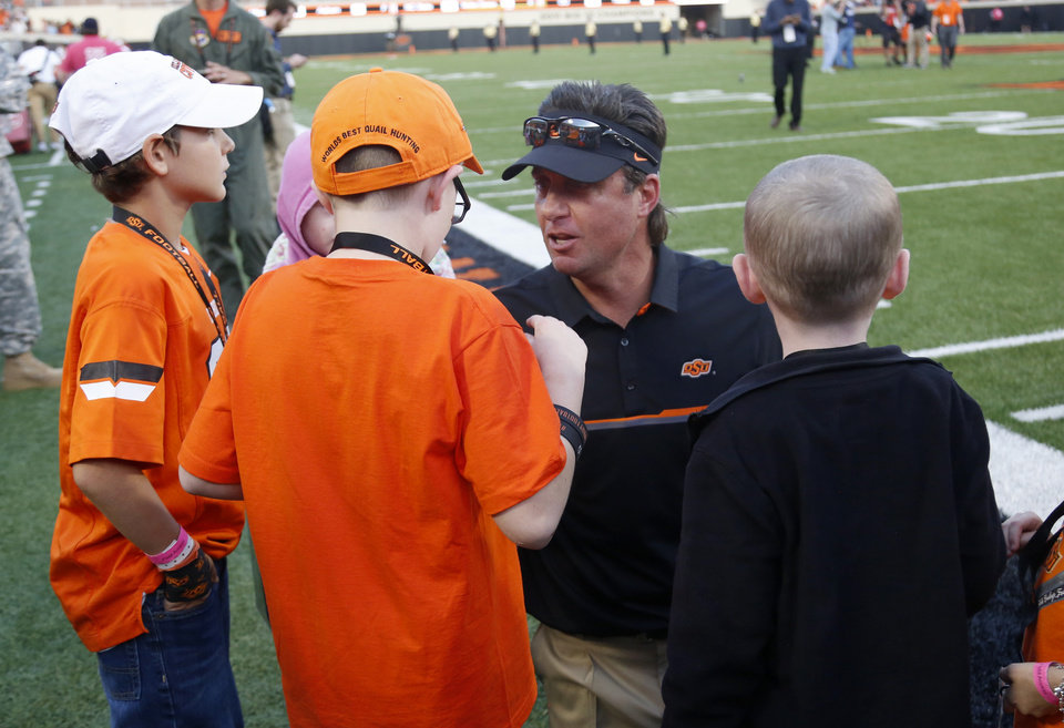 Photo - Oklahoma State head coach Mike Gundy talks with children from Coaches vs Cancer following a college football game between the Oklahoma State University Cowboys (OSU) and the Iowa State University at Boone Pickens Stadium in Stillwater, Okla., Saturday, Oct. 8, 2016. Photo by Sarah Phipps, The Oklahoman