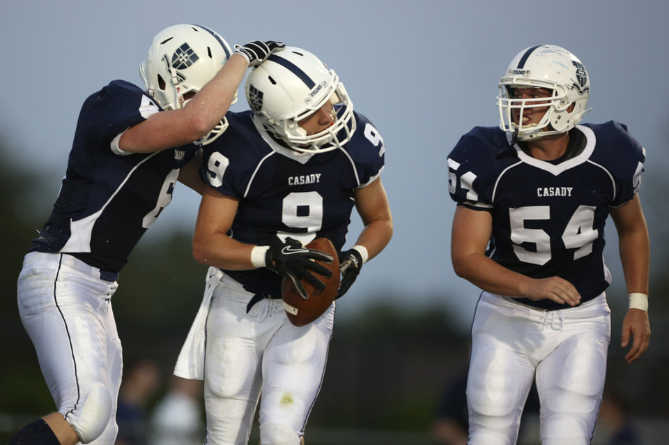Photo - Casady's Davis English (6) and Tripp Kerr (54) congratulate Trainor Crossno (9) after scoring during a game against Heritage Hall at Casady High School in The Village, Okla., Thursday, Aug. 30, 2012.  Photo by Garett Fisbeck, The Oklahoman