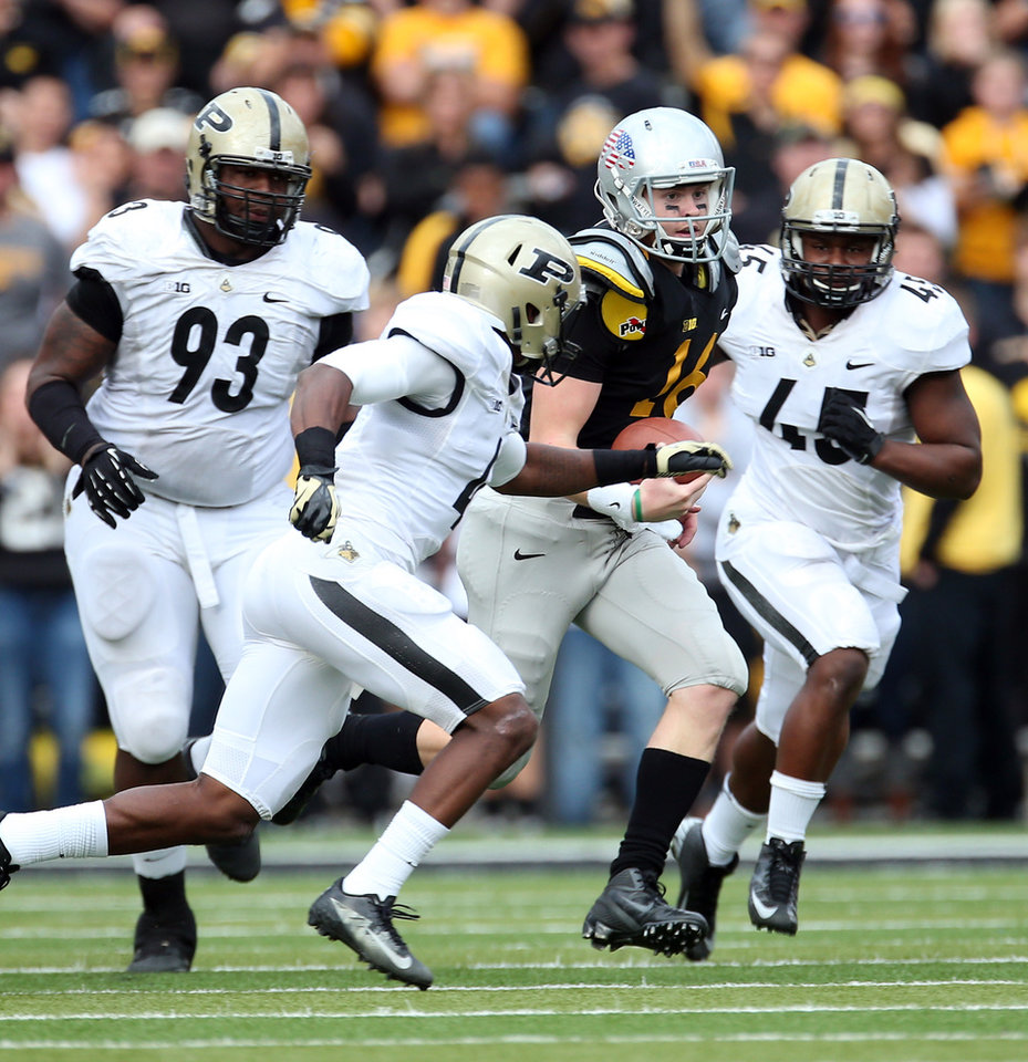 Iowa quarterback James Vandenberg (16) runs for 20 yards as Purdue defensive tackle Kawann Short (93), defensive back Taylor Richards (4) and linebacker Will Lucas (45) close in during the second halfo f of an NCAA college football game, Saturday, Nov. 10, 2012, in Iowa City, Iowa. Purdue won 27-24. (AP Photo/The Gazette, Liz Martin) MAGS OUT