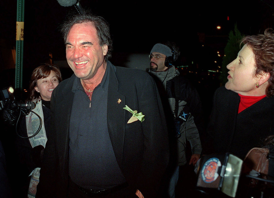 Photo - FILE - In this Nov. 19, 2000 file photo, American film director Oliver Stone laughs as he is approached by members of the media while leaving New York's Plaza Hotel, after attending the wedding of actor Michael Douglas and actress Catherine Zeta-Jones. Glitz overtook privacy when Douglas and Zeta-Jones brought old-fashioned glamour back for their swanky 2000 wedding. They married at The Plaza Hotel, drawing several hundred gawkers who craned to see inside arriving limos.  (AP Photo/Mitch Jacobson, file)