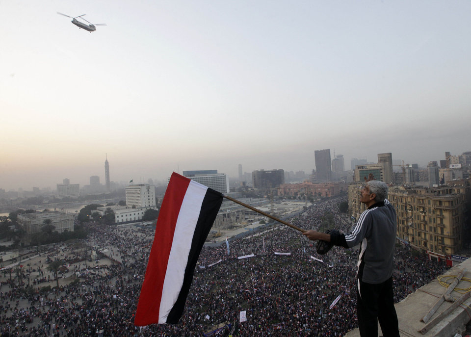 Photo - An Egyptian waves a national flag for a military helicopter flying over a pro-military rally marking the third anniversary of the 2011 uprising in Tahrir Square in Cairo, Egypt, Saturday, Jan. 25, 2014. Egyptian riot police have fired tear gas to disperse hundreds of supporters of ousted Islamist President Mohammed Morsi protesting as the country marks the third anniversary of the 2011 uprising, as supporters of the military gathered in rival rallies in other parts of the capital, many of them urging military chief Gen. Abdel-Fattah el-Sissi, the man who removed Morsi, to run for president. (AP Photo/Amr Nabil)