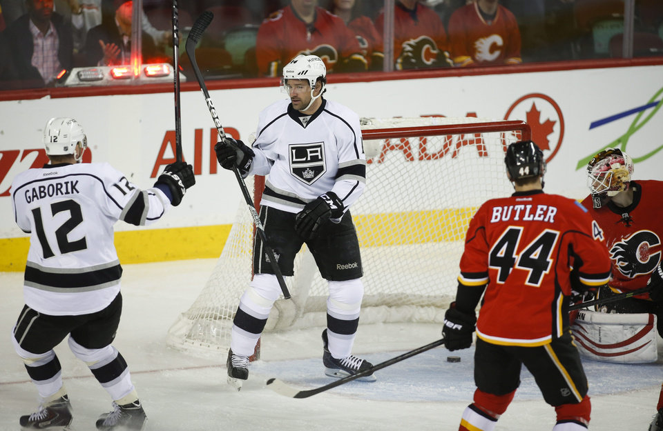 Photo - Los Angeles Kings' Justin Williams, center, celebrates his goal with teammate Marian Gaborik, left, from Slovakia, as Calgary Flames goalie Joni Ortio, right, from Finland, and Chris Butler look back at the puck during the first period of an NHL hockey game in Calgary, Alberta, Monday, March 10, 2014. (AP Photo/The Canadian Press, Jeff McIntosh)