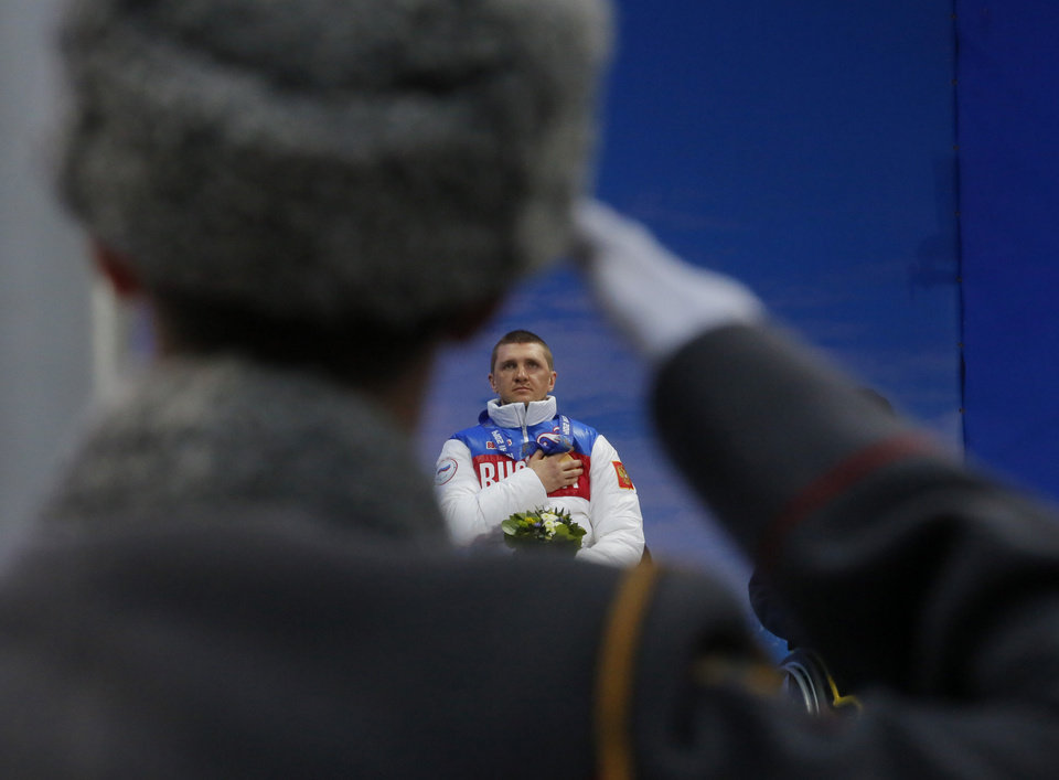 Photo - A Russian honor guard soldier salutes as Roman Petushkov of Russia, winner of the men's biathlon, 7.5km sitting event listens to the Russian national anthem during medal ceremony at the 2014 Winter Paralympic, Saturday, March 8, 2014, in Krasnaya Polyana, Russia. (AP Photo/Dmitry Lovetsky)