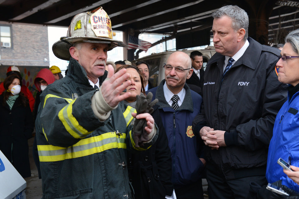 Photo - New York City Mayor Bill de Blasio, second from right, listens to a first responder near the site of a gas leak-triggered explosion in East Harlem, Thursday, March 13, 2014, in New York. Rescuers working amid gusty winds, cold temperatures and billowing smoke pulled additional bodies Thursday from the rubble of two apartment buildings that collapsed Wednesday. (AP Photo/The Daily News, Marcus Santos, Pool)