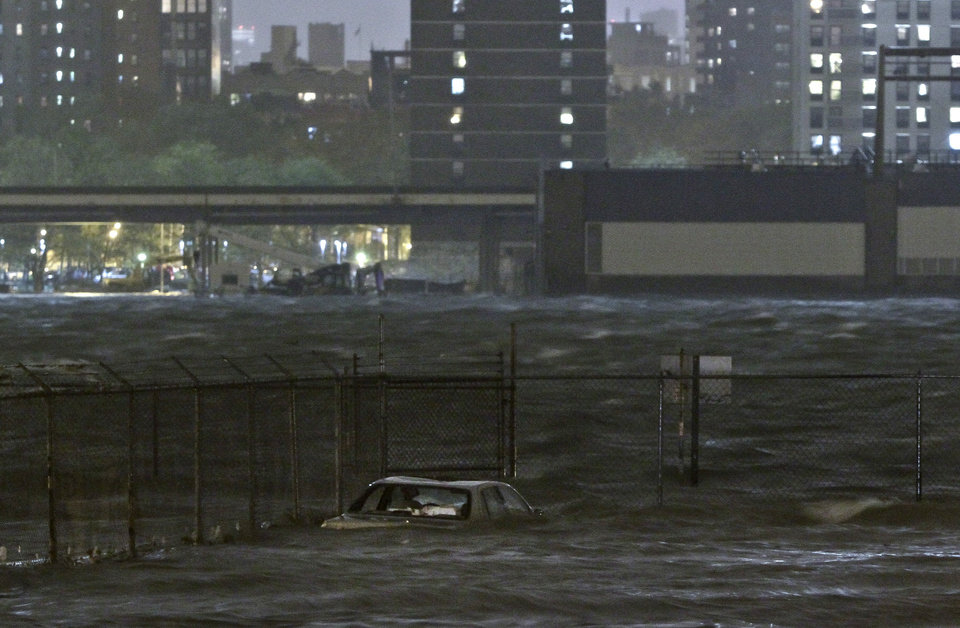 Photo -   A car is submerged in the Dumbo section of the Brooklyn borough of New York, as the East River overflows during hurricane Sandy, on Monday, Oct. 29, 2012. Authorities warned that New York City and Long Island could get the worst of the storm surge: an 11-foot onslaught of seawater that could swamp lower areas of the city. (AP Photo/Bebeto Matthews)