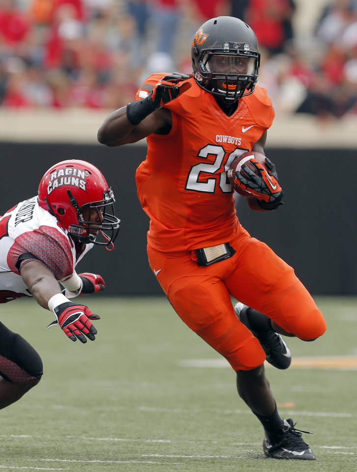 Oklahoma State\'s Desmond Roland (26) rushes as Louisiana-Lafayette\'s Tyren Alexander (29) tries to tackle him during a college football game between Oklahoma State University (OSU) and the University of Louisiana-Lafayette (ULL) at Boone Pickens Stadium in Stillwater, Okla., Saturday, Sept. 15, 2012. Photo by Sarah Phipps, The Oklahoman