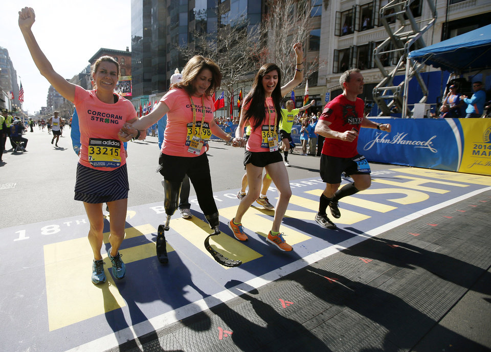 Photo - Double amputee Celeste Corcoran, center, a victim of last year's bombings, reaches the finish line of the 118th Boston Marathon, Monday, April 21, 2014, in Boston, with the aid her sister Carmen Acabbo, left, and daughter Sydney, right, who was also wounded last year. (AP Photo/Elise Amendola)