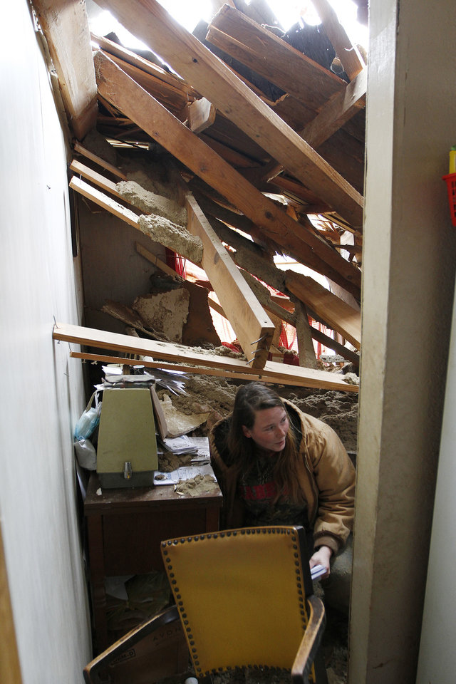 Audrey Boykin salvages personal items from the caved in home of Dorothy Dixon in Centreville, Miss. on Wednesday, Dec. 26, 2012. A tree fell into the home, but no one was home at the time the tree fell on Dixon's home, except for Dixon's dogs who were unharmed. More than 25 people were injured and at least 70 homes were damaged in Mississippi by the severe storms that pushed across the South on Christmas Day, authorities said Wednesday. (AP Photo/The Enterprise-Journal, Philip Hall)