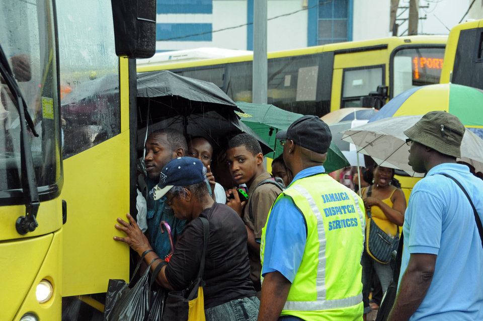 Photo -   Commuters board a bus as rain brought by the outer bands of Tropical Storm Sandy fall in Kingston, Jamaica, Tuesday, Oct. 23, 2012. The U.S. National Hurricane Center in Miami said Sandy was expected to become a hurricane as it nears Jamaica on Wednesday. (AP Photo/Collin Reid)