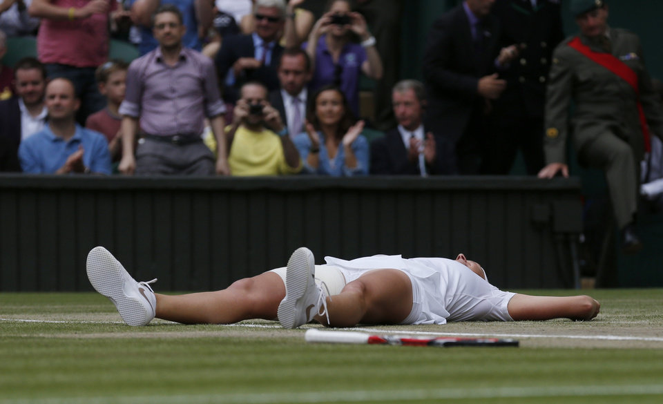 Photo - Petra Kvitova of Czech Republic lays on the court as she celebrates defeating Eugenie Bouchard of Canada in their women's singles final at the All England Lawn Tennis Championships in Wimbledon, London, Saturday July 5, 2014. (AP Photo/Sang Tan)