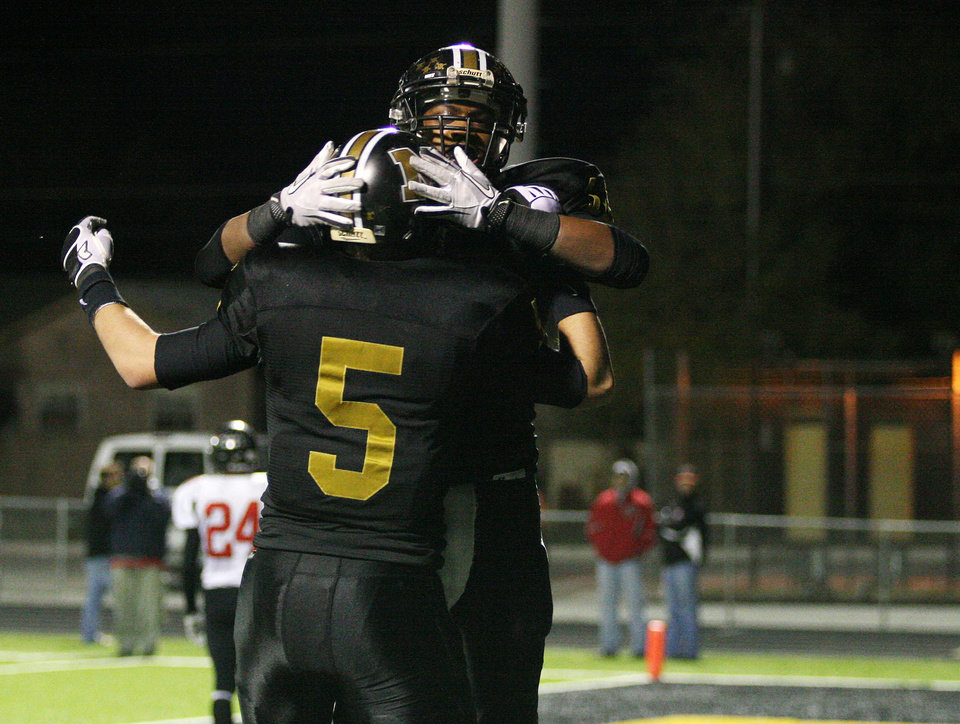 Photo - Midwest City's Zac Brannon (5) and Cornell Neal (12) celebrate after a touchdown during a high school football game between Midwest City and Westmoore in Midwest City, Friday, Nov. 11, 2011.  Photo by Garett Fisbeck, for The Oklahoman
