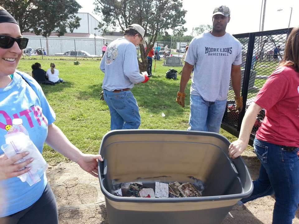 Volunteers use a plastic tub to gather lost photographs in hopes of saving them for families affected by the tornado. STAFF PHOTO BY ED GODFREY, THE OKLAHOMAN