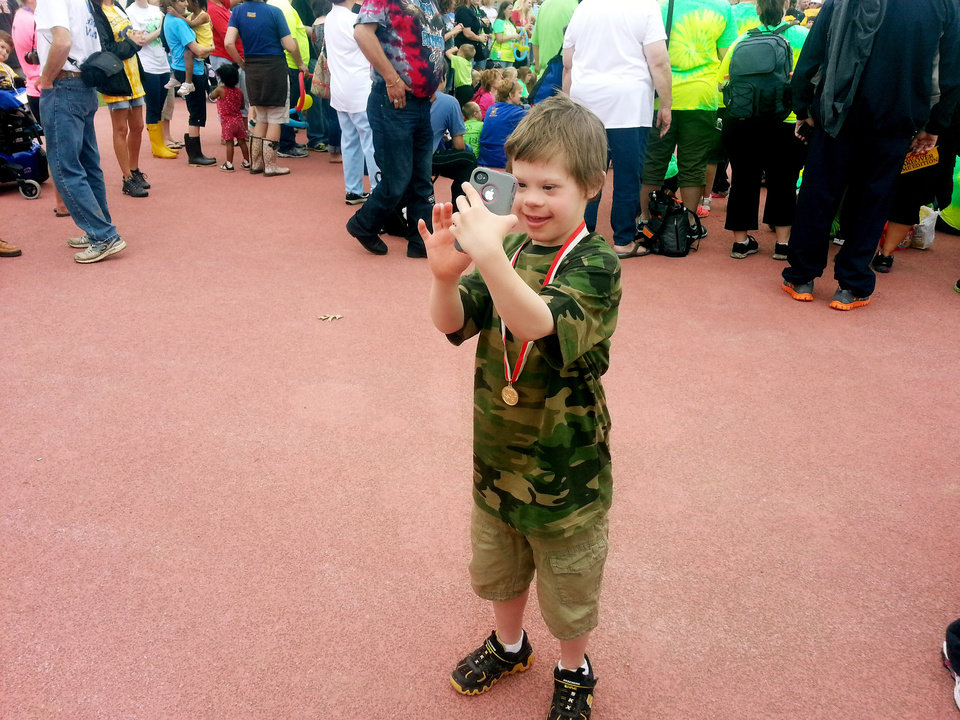 Photo of Cade Godfrey taking photos with an iPhone at the Oklahoma Special Olympics Summer Games in Stillwater May 9, 2013. Photo by Ed Godfrey, The Oklahoman