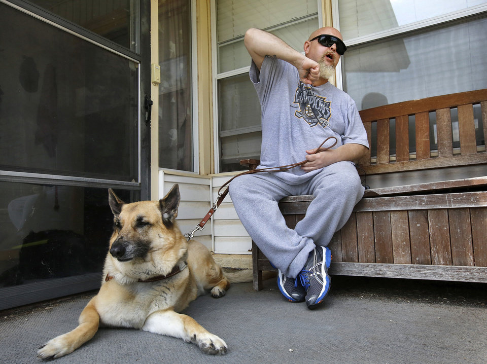 Photo - Gordan Allen Besaw, a blind veteran, recounts how he defended himself against his attacker as he sits on the front porch of his home with his service dog, Derby, Wednesday afternoon, May 1, 2013.  Besaw was attacked earlier this week when walking to a bus stop with his seeing eye dog. He said he relied on Army training to take down his attacker who was arrested by police.  Besaw was not injured. He lives near NW 23 and Donald  in Bethany. Photo  by Jim Beckel, The Oklahoman.