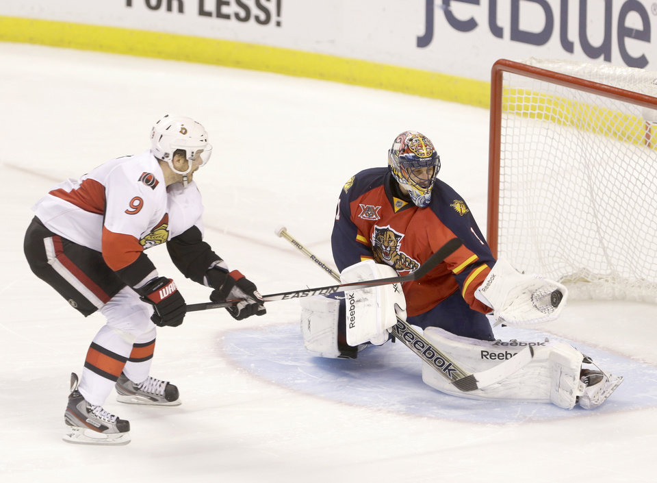 Photo - Florida Panthers goalie Roberto Luongo (1) makes a save against Ottawa Senators left wing Milan Michalek (9) of the Czech Republic, during a shootout in an NHL hockey game, Tuesday, March 25, 2014 in Sunrise, Fla. The Panthers defeated the Senators 3-2. (AP Photo/Wilfredo Lee)