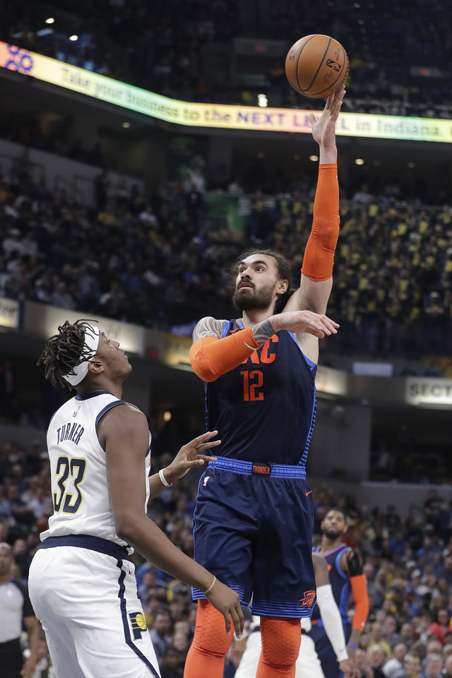 Photo - Oklahoma City Thunder's Steven Adams (12) shoots over Indiana Pacers' Myles Turner (33) during the first half of an NBA basketball game, Thursday, March 14, 2019, in Indianapolis. (AP Photo/Darron Cummings)