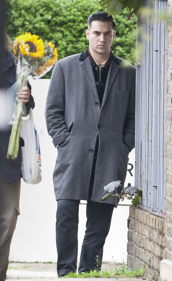 Photo - British singer and filmmaker Reg Traviss looks on as a member of the public passes to lay flowers near a police cordon by Camden Square, close to the home of British singer Amy Winehouse, who was found dead, Saturday, July 23, 2011.  Traviss and Winehouse are known to have a close relationship.  The cause of death was not immediately known, and London Ambulance Services said Winehouse had died before the two ambulance crews arrived at the scene.(AP Photo/Joel Ryan) ORG XMIT: LENT102