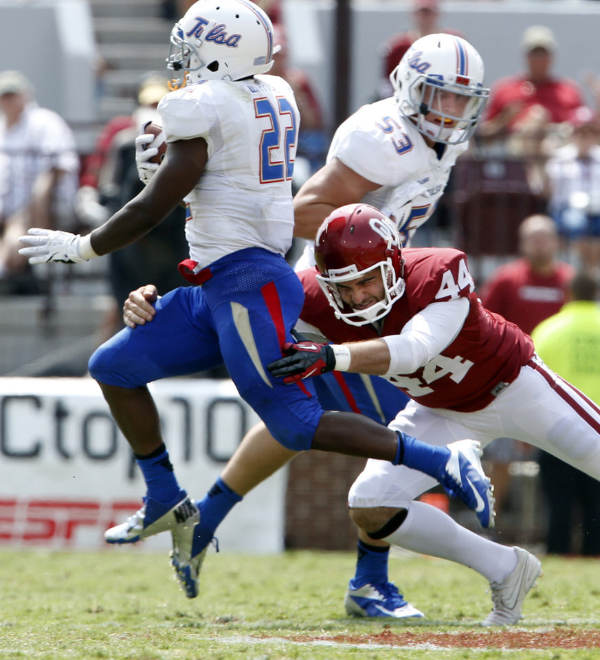 Photo - Tulsa's Trey Watts (22) slips a tackle by Jed Barnett on his way to a long gain during the second half of a college football game between the University of Oklahoma Sooners (OU) and the Tulsa Golden Hurricane (TU) at Gaylord Family-Oklahoma Memorial Stadium in Norman, Okla., on Saturday, Sept. 14, 2013. Photo by Steve Sisney, The Oklahoman