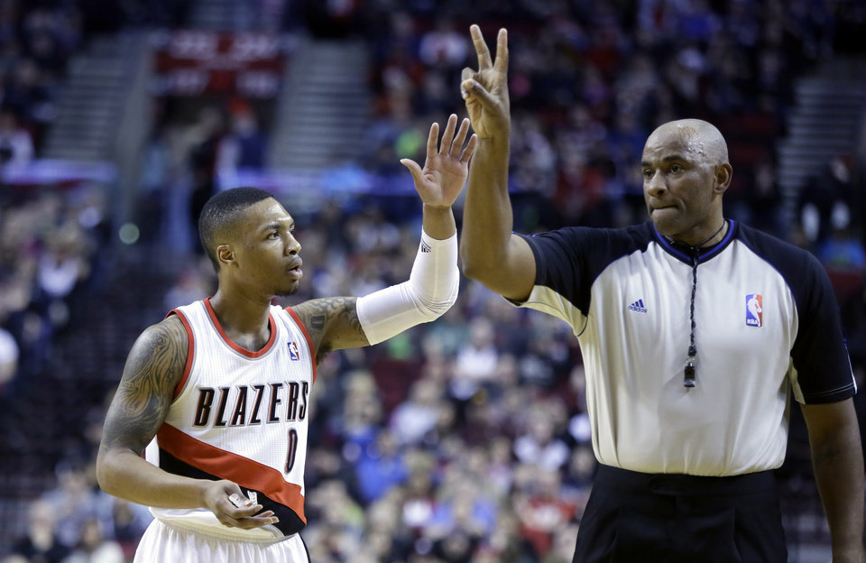 Photo - Portland Trail Blazers guard Damian Lillard, left, complains as he is called for a foul by referee Kevin Cutler during the first half of an NBA basketball game against the Washington Wizards in Portland, Ore., Thursday, March 20, 2014. (AP Photo/Don Ryan)
