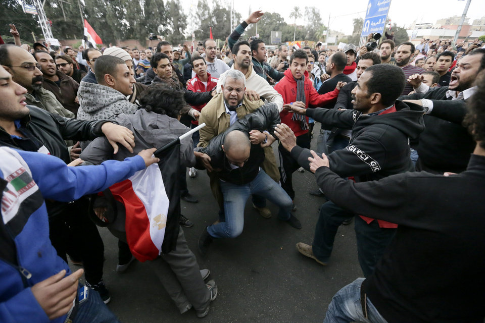 Photo - FILE - In this Wednesday, Dec. 5, 2012 file photo, Egyptian President Mohammed Morsi's supporters beat an opponent, center, during clashes outside the presidential palace, in Cairo, Egypt. Egypt's Islamist president makes good on vows of action against opponents, as the top prosecutor issues arrest warrants against five prominent activists and summons opposition politicians for questioning over weekend clashes between the Muslim Brotherhood and protesters. (AP Photo/Hassan Ammar, File)