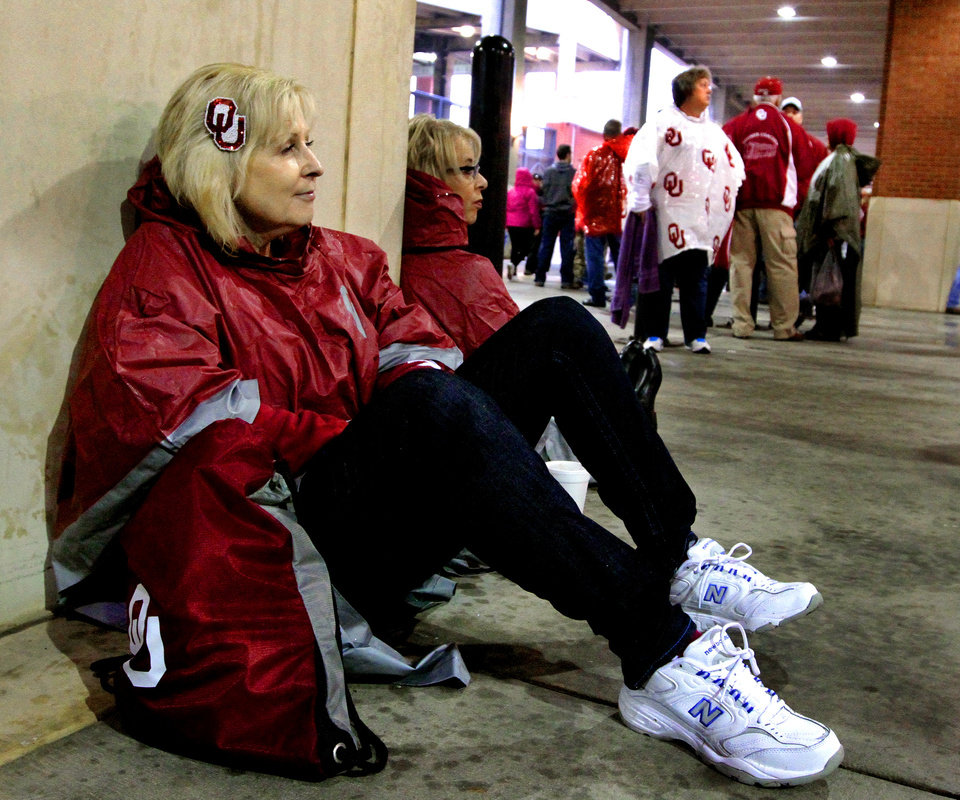 Debbie Lermy, Tulsa, waits with other fans under the covered garage as rain and the threat of lightning delay a college football game between the University of Oklahoma Sooners (OU) and the Texas Tech Red Raiders at Gaylord Family-Oklahoma Memorial Stadium in Norman, Okla., on Saturday, Oct. 26, 2013. Photo by Steve Sisney, The Oklahoman