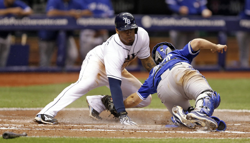 Photo - Tampa Bay Rays' Desmond Jennings, left, sores past the tag of Toronto Blue Jays catcher Josh Thole during the fifth inning of a baseball game Monday, March 31, 2014, in St. Petersburg, Fla. Jennings scored on a double by Matt Joyce. (AP Photo/Chris O'Meara)