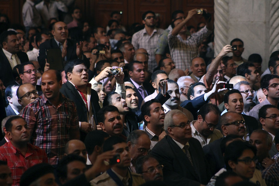 Egyptian Copts react following the announcement of the name of Bishop Tawadros, soon to be Pope Tawadros II, during the papal election ceremony at the Coptic Cathedral in Cairo, Egypt, Sunday, Nov. 4, 2012. Egypt's ancient Coptic Christian church chose a new pope in an elaborate Sunday ceremony meant to invoke the will of God, in which a blindfolded boy drew the name of the next patriarch from a crystal chalice. Bishop Tawadros will be ordained Nov. 18, 2012 becoming the spiritual leader of a community that increasingly fears for its future amid the rise of Islamists to power in the wake of the 2011 ouster of longtime authoritarian leader Hosni Mubarak. (AP Photo/Roger Anis, )