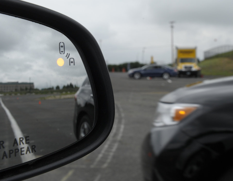 Photo -   In this photo taken, Tuesday, May 22, 2012, professional test driver J.D. Ellis of Cincinnati, Ohio, demonstrates the side mirror warning signal in a Ford Taurus at an automobile testing area in Oxon Hill, Md. The display at a recent transportation conference was a peek into the future of automotive safety: cars that to talk to each other and warn drivers of impending collisions. Later this summer, the government is launching a yearlong, real-world test involving nearly 3,000 cars, trucks and buses using volunteer drivers in Ann Arbor, Mich. (AP Photo/Susan Walsh)