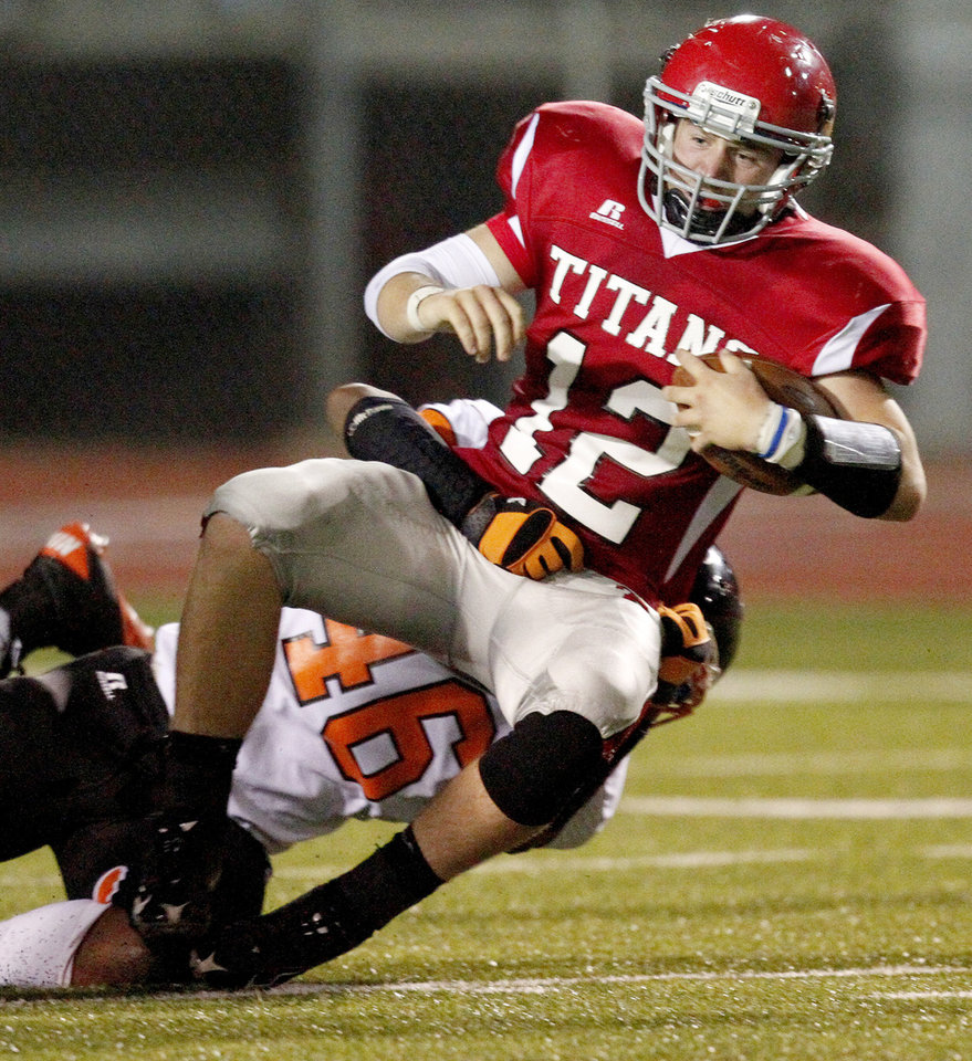 Photo - Carl Albert's Taylor Hawkins is brought down by Hollis Birmingham of Booker T. Washington during a high school football game in Midwest City, Okla., Friday, September 3, 2010.  Photo by Bryan Terry, The Oklahoman