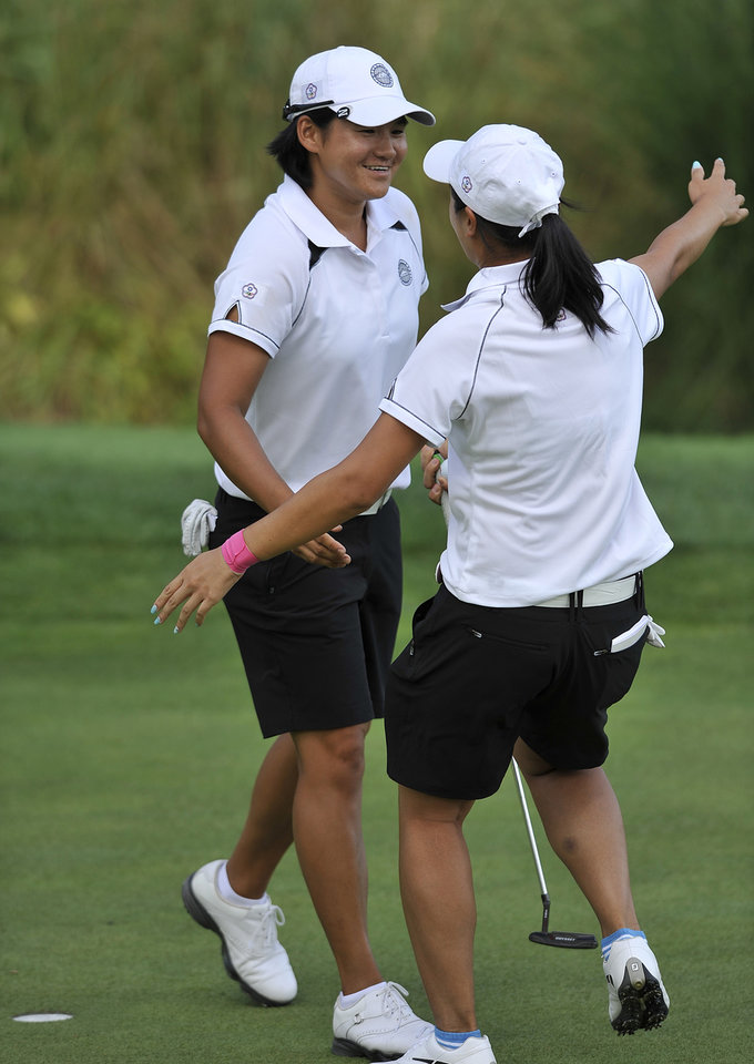 Photo - Yani Tseng,left, of Taiwan celebrates with teammate Phoebe Yao after she birded the 18th hole during the first round of the International Crown LPGA golf tournament Thursday, July 24, 2014, in Owings Mills, Md.(AP Photo/Gail Burton)