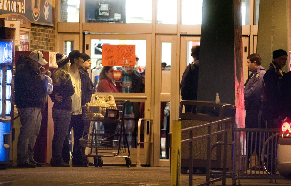Photo - Bystanders watch as Topeka police investigate at the scene of a shooting outside a grocery store in Topeka, Kan., Sunday, Dec. 16, 2012. Two Kansas police officers were shot outside the store on Sunday while responding to a report of a suspicious vehicle and died later at a hospital, authorities said. (AP Photo/The Topeka Capital Journal, Thad Allton)