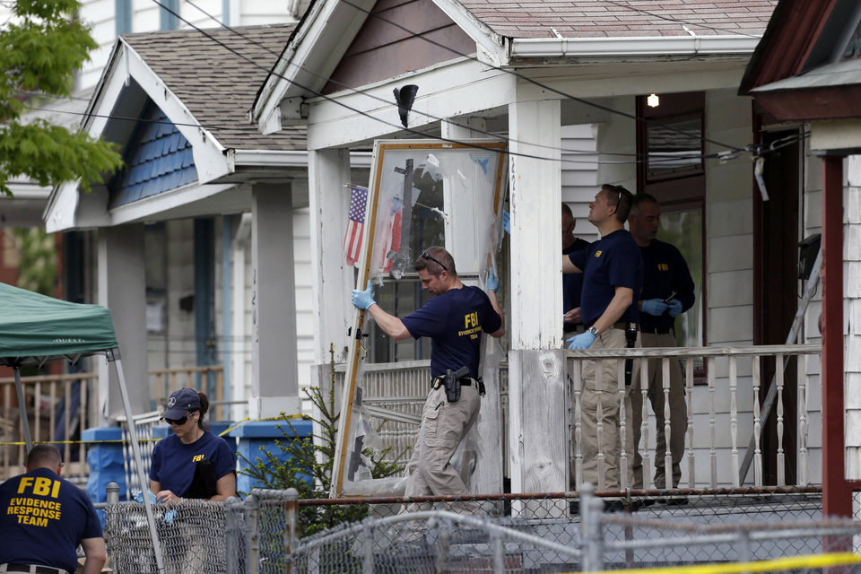 Photo - FILE - In this May 7, 2013 file photo, members of the FBI evidence response team carry out the front screen door from the Cleveland home of Ariel Castro, where three women escaped after 10 years of captivity. Amanda Berry broke through the screen door to freedom last May. Upstairs, officers found Gina DeJesus and Michelle Knight. They had been snatched off the streets separately between 2002 and 2004 and locked inside Castro's house where he chained and raped them, investigators later said. (AP Photo/Tony Dejak, File)